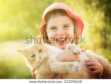 Happy little girl with kitten outside.
