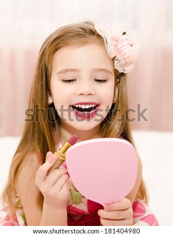 Happy little girl with lipstick and  mirror  - stock photo