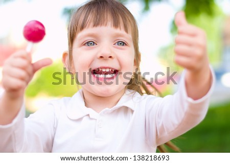 Happy little girl with lollipop outdoors