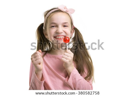 Happy little girl with lollipop smiling. Girl wearirng pink t-shirt and pink hair bend - stock photo