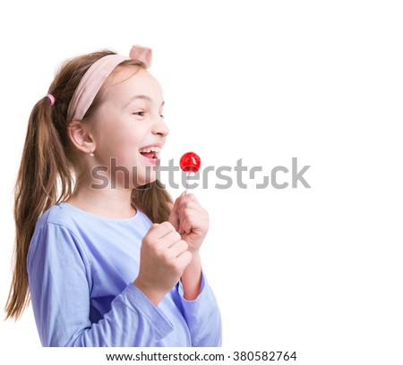 Happy little girl with lollipop smiling. She  is wearing pink t-shirt and pink hair bend - stock photo