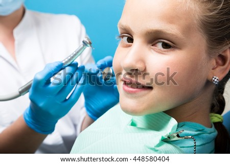 happy little girl with open mouth undergoing dental treatment at clinic. Dentist checked and curing teeth a child patient in the dental office - stock photo