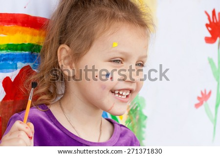happy little girl with paint brush and painting - stock photo