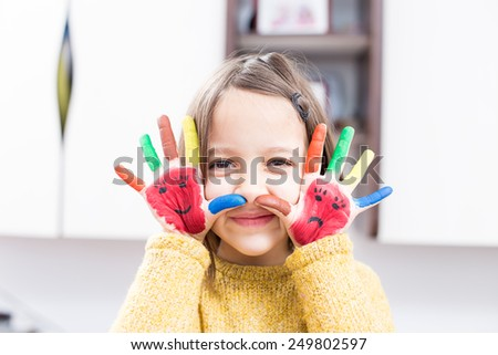 Happy little girl with painted hand