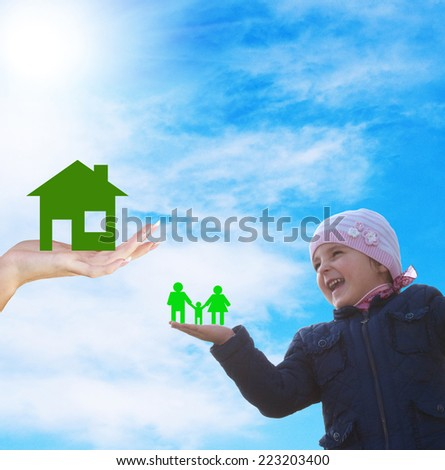 Happy little girl with paper family on hand.New home for family - stock photo