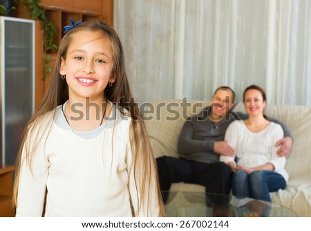Happy little girl with parents posing in livingroom at home and smiling - stock photo