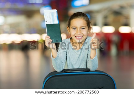 happy little girl with passport and ticket giving thumb up at airport - stock photo