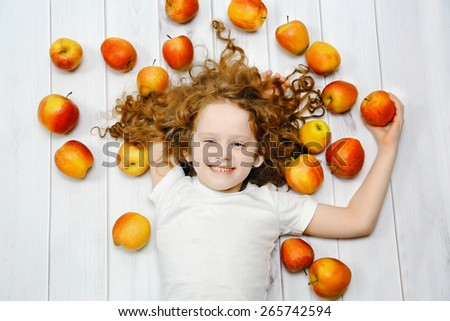 Happy little girl with red apples on light wooden floor. Top view. - stock photo
