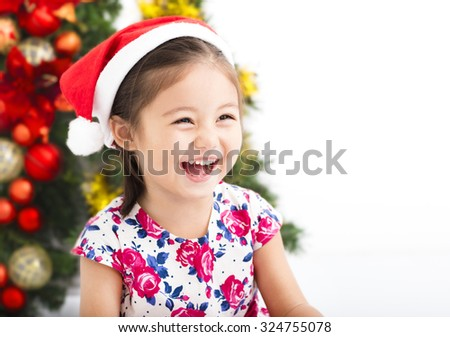 happy little girl  with Santa red hat in front of  christmas tree - stock photo