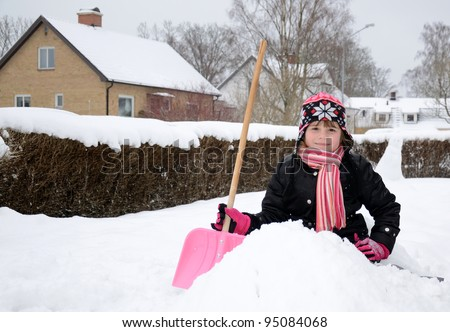 Happy little girl with snow shovel - stock photo