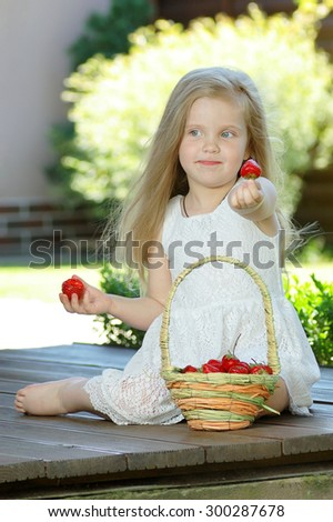 happy little girl with strawberries - stock photo