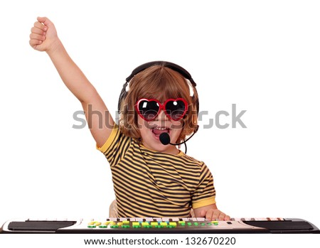 happy little girl with sunglasses play keyboard and sing - stock photo