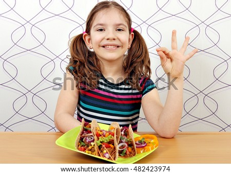 happy little girl with tacos and ok hand sign