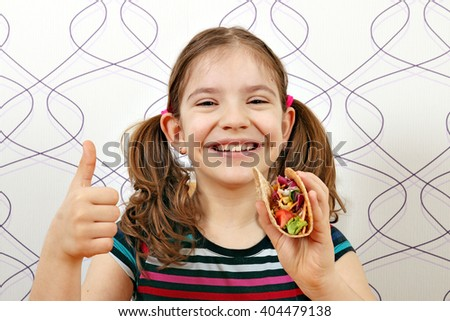 happy little girl with tacos and thumb up - stock photo