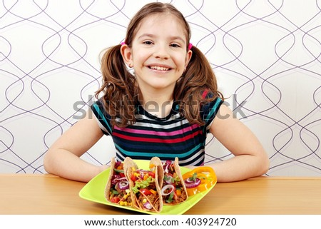 happy little girl with tacos on plate - stock photo
