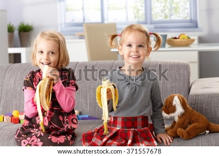 Happy little girls eating banana at home, sitting on sofa, smiling.