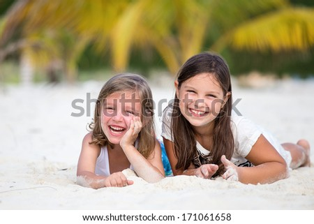 Happy little girls enjoy summer day at the beach - stock photo