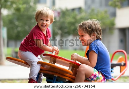 Happy little girls having fun at playground in sunny day