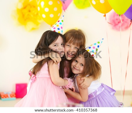 Happy little girls hugging at birthday party - stock photo