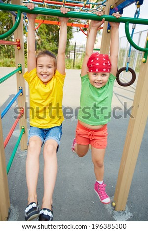 Happy little girls looking at camera on playground area - stock photo