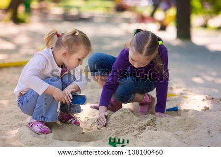 Happy little girls playing in a sandbox on the playground - stock photo