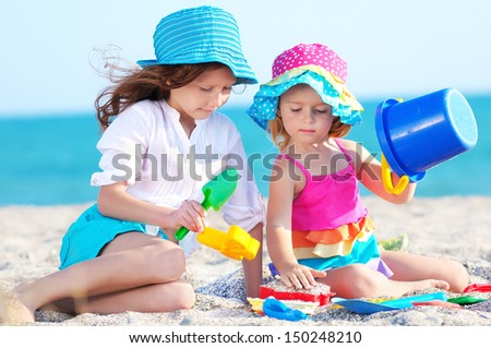 Happy little girls playing on beach - stock photo