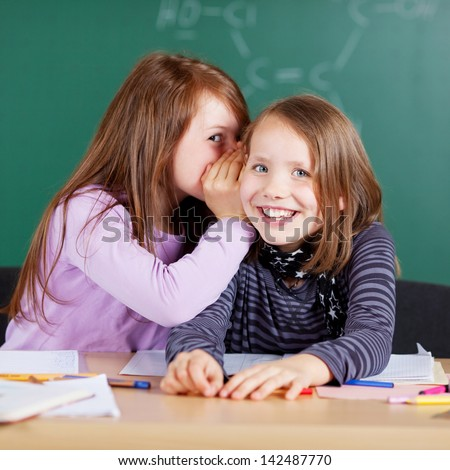 Happy little girls sharing a secret smiling in glee as they whisper together sharing a secret - stock photo