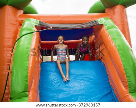 Happy little girls sliding down an inflatable bounce house