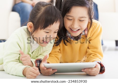 happy little girls using tablet computer - stock photo