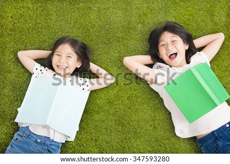 happy Little  girls with book and resting on the grass - stock photo