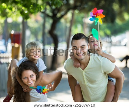 Happy little girls with windmills sitting on smiling parent's arms outdoor  - stock photo