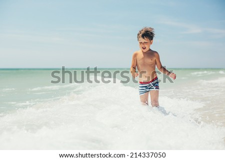 happy little happy boy playing at sea