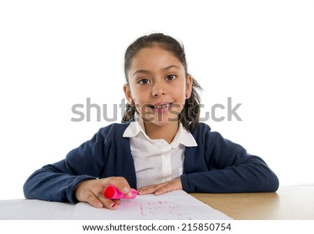 Happy little hispanic female girl studying writing homework with marker on notepad with notebook on desk smiling in children education and back to school concept isolated on white background - stock photo