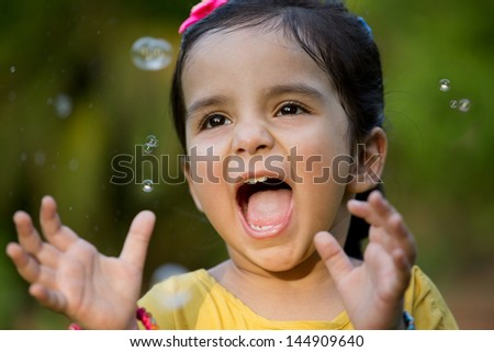 happy little Indian girl playing with bubbles - stock photo