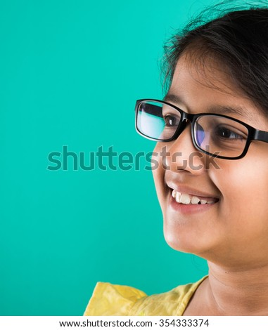 Happy little indian girl smiling while wearing glasses, green background, indian small girl wearing glass, asian small girl and glasses, 10 year old girl, extreme closeup or close up - stock photo