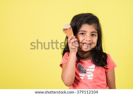 happy Little Indian girl with an ice cream cone in hand, asian girl and ice cream - stock photo