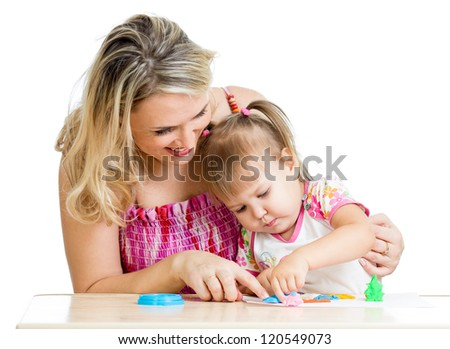 Happy little kid and mother sitting at table and playing with colorful clay toy