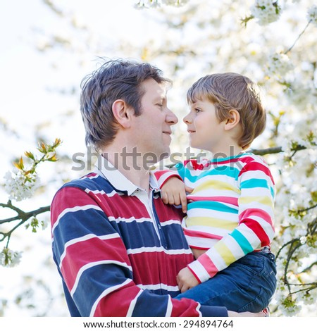 Happy little kid boy and his dad in blooming cherry garden in spring. Happy family celebrating father's day. - stock photo