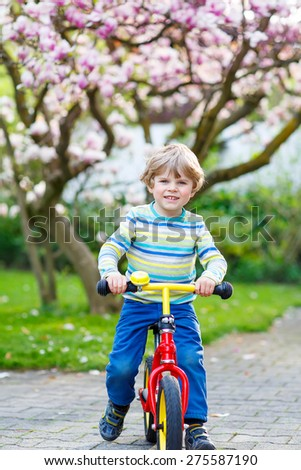 Happy little kid boy biking with his first bike in park or garden on warm spring day. Happy child in colorful clothes. Active leisure for kids outdoors. - stock photo