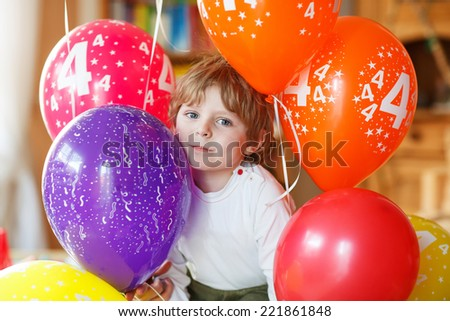 Happy little kid boy celebrating his 4 birthday with colorful balloons, indoor in kidsroom. - stock photo