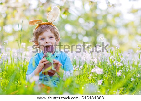 Happy little kid boy eating chocolate and wearing Easter bunny ears, sitting after egg hunt in blooming garden on warm sunny day. Celebrating Easter traditional holiday.