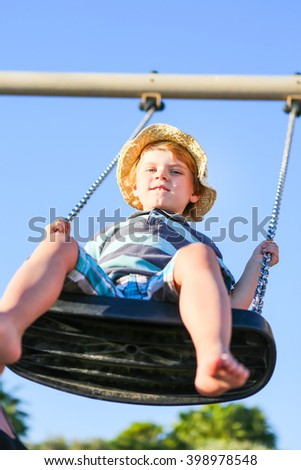 Happy little kid boy having fun on chain swing. Toddler child smiling and laughing on playground on Summer day. - stock photo