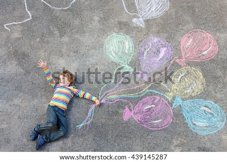 Happy little kid boy having fun with colorful balloons picture drawing with colorful chalks. Creative leisure for children outdoors in summer