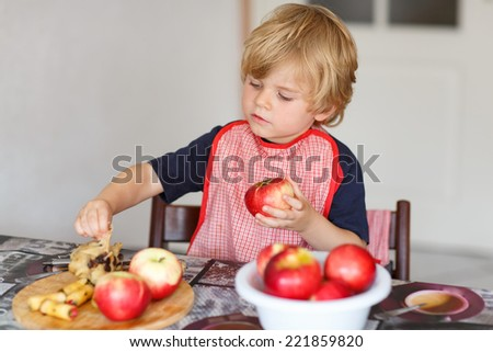 Happy little kid boy helping and baking apple pie in home''s kitchen, indoor. Filling apple with marzipan