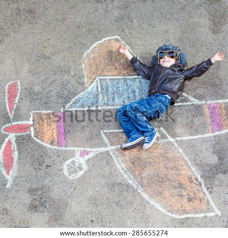 Happy little kid boy in pilot uniform having fun with airplane picture drawing with colorful chalk. Creative leisure for children outdoors in summer. - stock photo
