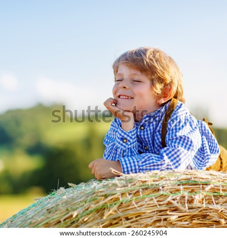 Happy little kid boy in traditional German bavarian clothes, leather shorts and check shirt,  lying on hay stack or bale and dreaming. Active outdoors leisure with children on warm summer day. - stock photo