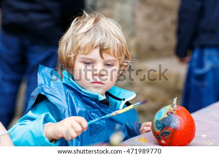 Happy little kid boy on a harvest festival, painting with colors a pumpkin. Child celebrating traditional festival halloween or thanksgiving.