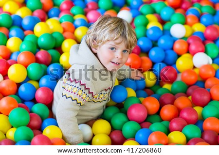 Happy little kid boy playing at colorful plastic balls playground high view. Funny child having fun indoors.