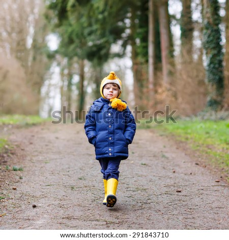 Happy little kid boy walking through autumn forest. Child in yellow waterproof rainboots. Active leisure with kids outdoors. - stock photo