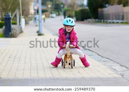Happy little kid, cute blonde toddler girl in pink jacket and blue safety helmet playing outdoors on the street riding her push bike, wooden horse with three wheels - stock photo